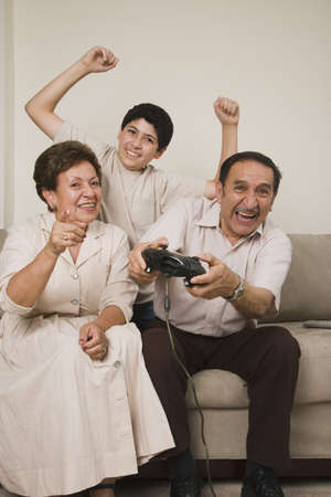 playing on divan: Hispanic grandparents and grandson playing video games