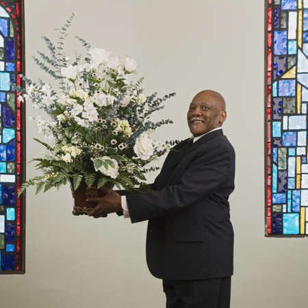 vicar: African man holding flower bouquet in church