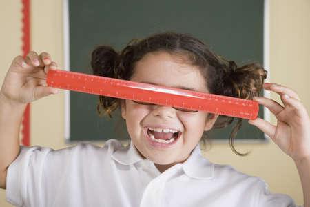 holding close: Hispanic girl holding ruler over eyes LANG_EVOIMAGES