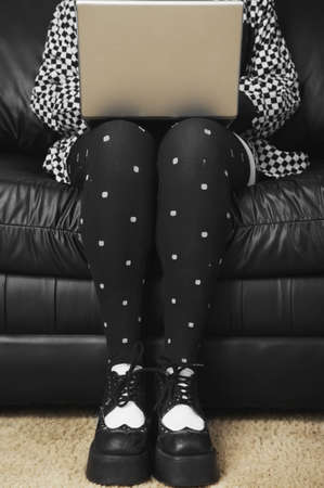Woman in funky tights typing on laptop Stock Photo - 16094689