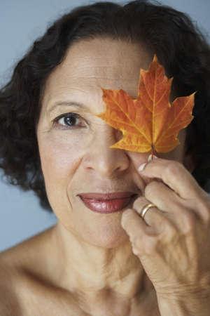 babyboomer: Senior African woman holding autumn leaf over eye LANG_EVOIMAGES