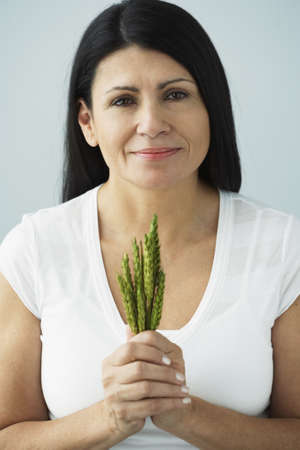 middle eastern woman: Hispanic woman holding bunch of grain