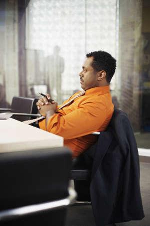 spectating: African businessman sitting at desk