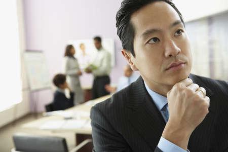 unconcerned: Asian businessman thinking LANG_EVOIMAGES