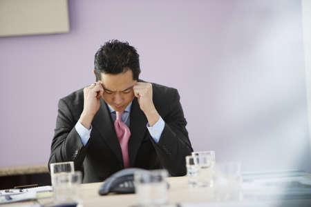 seated man: Hombre de negocios asiático con la cabeza entre las manos
