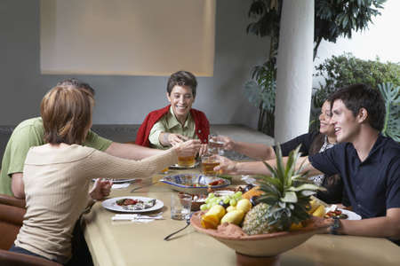 dining table and chairs: Family toasting at dinner table LANG_EVOIMAGES