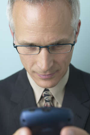 electronic organizer: Middle-aged businessman looking at cell phone LANG_EVOIMAGES