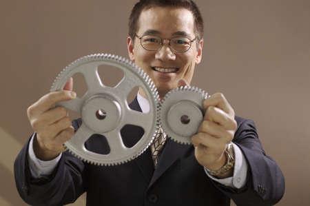 Asian businessman holding gear wheels Stock Photo - 16094822