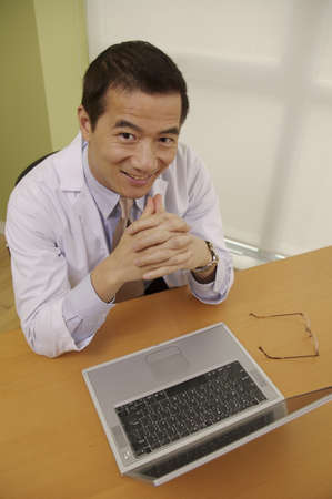 Asian businessman next to laptop Stock Photo - 16094824