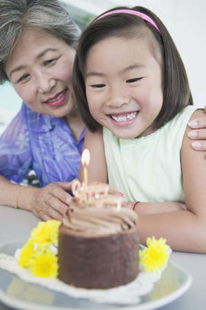 gramma: Asian girl celebrating birthday with grandmother LANG_EVOIMAGES