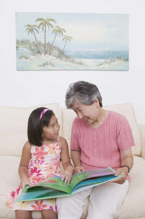 gramma: Asian grandmother and granddaughter reading book