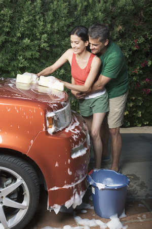 car wash: Hispanic couple washing car in driveway LANG_EVOIMAGES