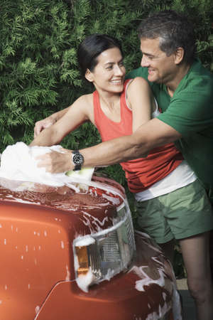 Hispanic couple washing car in driveway Stock Photo - 16094830