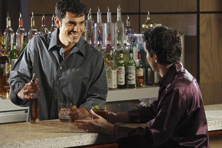 food industry: Hispanic male bartender talking to customer