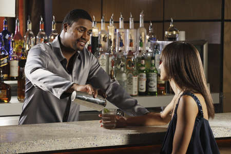 barkeep: African male bartender pouring drink