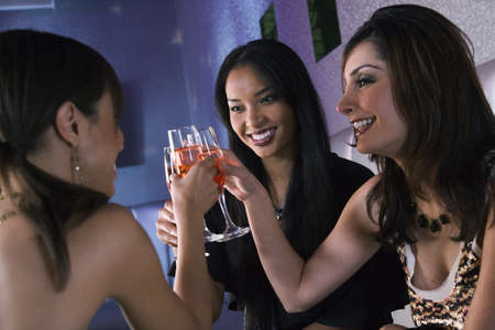 sipping: Multi-ethnic women toasting with cocktails