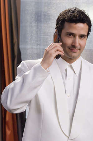 Hispanic man in tuxedo talking on cell phone Stock Photo - 16094845