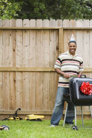 African man wearing party hat and barbequing Stock Photo - 16094854