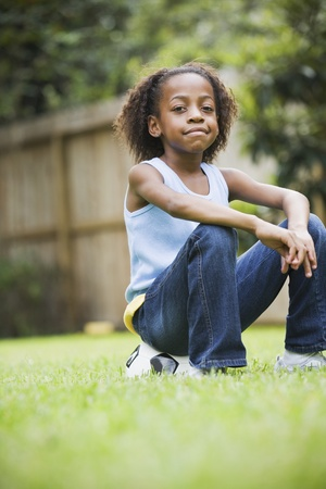 tomboy: African girl sitting on soccer ball