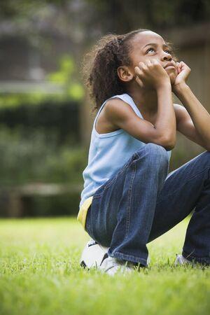 African girl sitting on soccer ball Stock Photo - 16092409