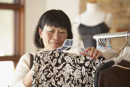 babyboomer: Senior Asian woman shopping for clothing LANG_EVOIMAGES
