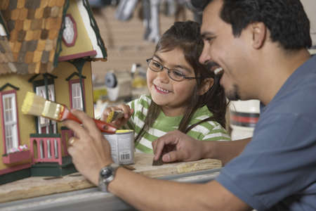 Hispanic father and daughter painting doll house