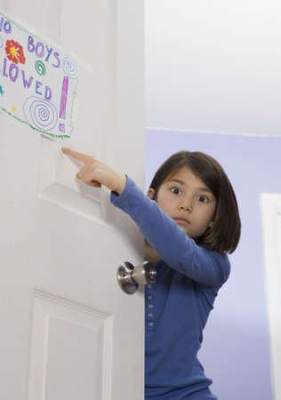 low spirited: Asian girl pointing at sign on bedroom door