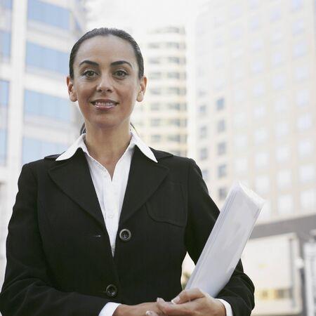 Hispanic businesswoman holding paperwork Stock Photo - 16094896