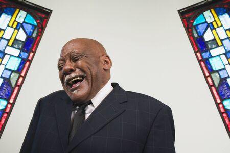 pastor: Senior African man laughing in church LANG_EVOIMAGES