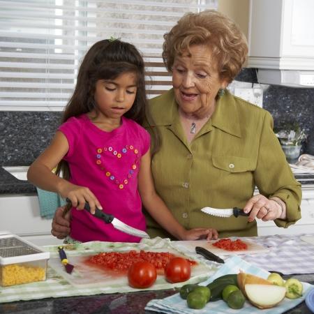 cooking implement: Hispanic grandmother and granddaughter preparing food