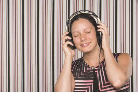 filipino ethnicity: Filipino woman listening to headphones LANG_EVOIMAGES