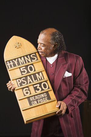 principled: Senior African man holding hymn board LANG_EVOIMAGES
