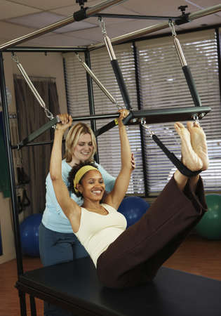 exerting: African woman exercising with personal trainer