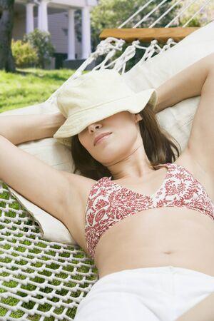 arms behind head: Woman laying in hammock