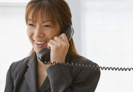 acknowledging: Asian businesswoman talking on telephone