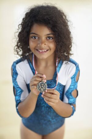 prevailing: Young female gymnast wearing medal LANG_EVOIMAGES