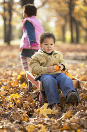 cooperating: African girl pulling brother in wagon