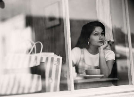 considering: Woman looking out cafe window LANG_EVOIMAGES