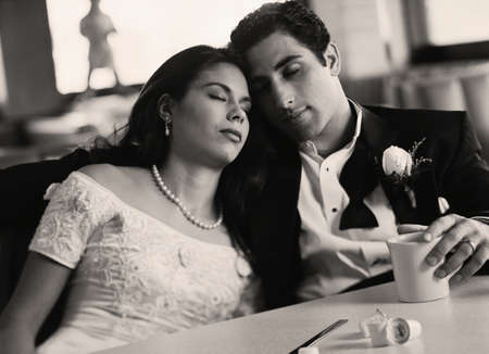 wearying: Bride and groom with eyes closed at diner LANG_EVOIMAGES