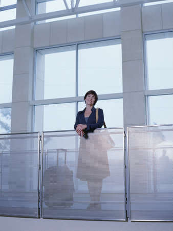 balcony: Woman leaning on railing at airport