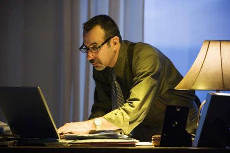 late 50s: Hispanic businessman typing on laptop