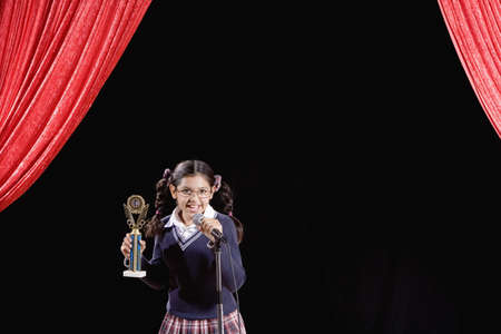 prevailing: Hispanic girl holding trophy on stage
