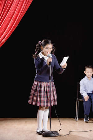 Hispanic girl reading from paper on stage