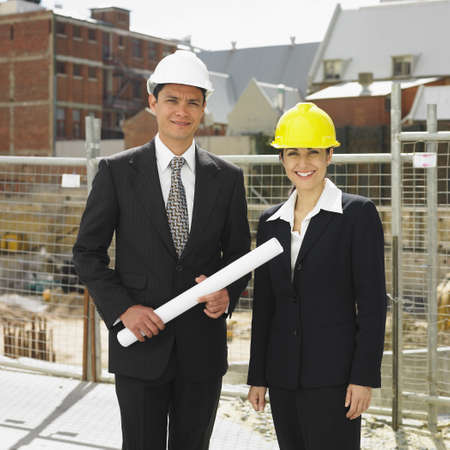 attired: Businesspeople wearing hard hats at construction site LANG_EVOIMAGES