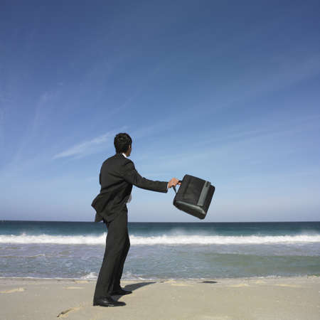 wearying: Hispanic businessman throwing briefcase at beach LANG_EVOIMAGES