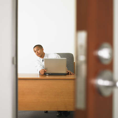 nosey: Mixed Race businessman looking out from desk LANG_EVOIMAGES