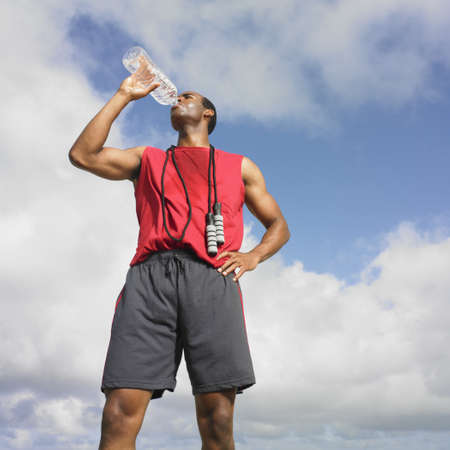 man drinking water: African man drinking from water bottle