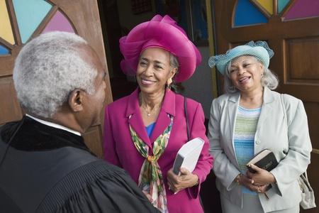 congregation: Senior African American women talking to Reverend LANG_EVOIMAGES