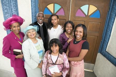 Afro-Amerikaanse dominee en parochianen in de voorkant van de kerk