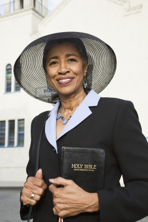 one mid adult woman only: Senior African American woman in front of church